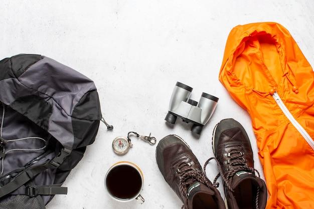 Reisrugzak, kompas, laarzen, jas, camera en verrekijker op een witte achtergrond. concept wandeling, toerisme, kamp. Premium Foto