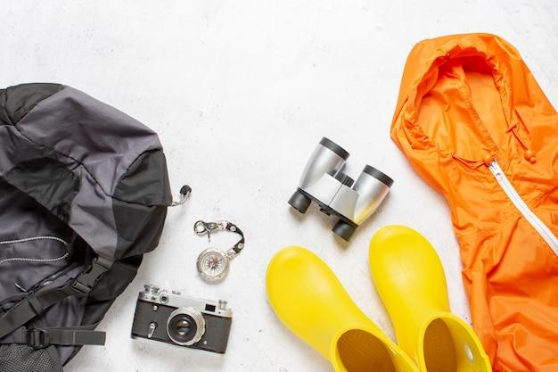 Reisrugzak, kompas, rubberen laarzen, jas, camera en verrekijker op een witte achtergrond. concept van wandelen, toerisme, kamp, bergen, bos. Premium Foto