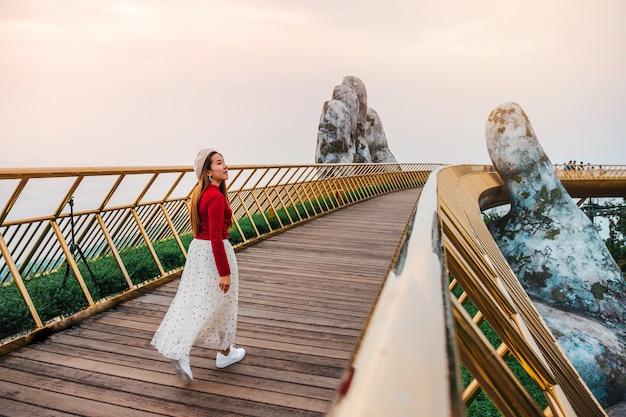 Reisvrouw bij gouden brug in ba na-heuvels, danang vietnam Premium Foto