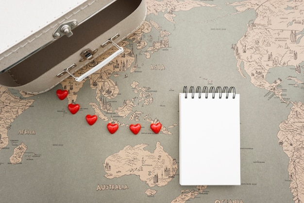 Reizen achtergrond met koffer en leeg notitieboekje Gratis Foto