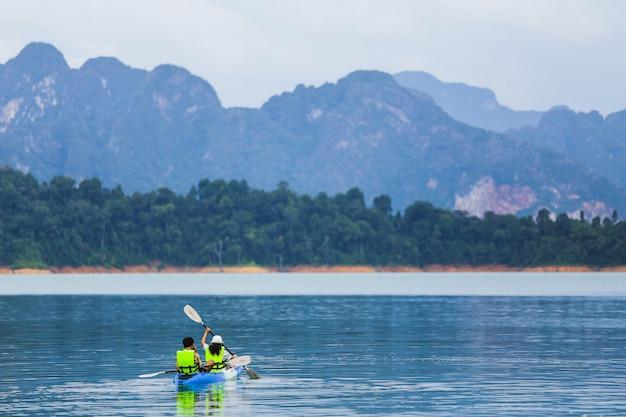 Reizen en huwelijksreis kajakken en kanoën met geliefde. uitzicht op bergen Premium Foto