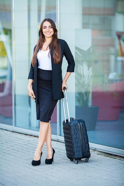 Reizen, jonge vrouw gaat op luchthaven venster met koffer wachten op vliegtuig Premium Foto