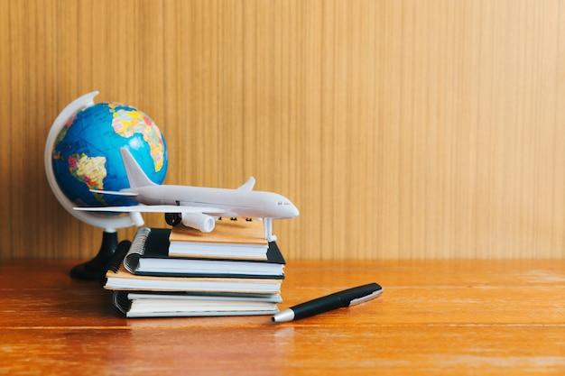 Reizen, reis vakantie, close-up van speelgoed vliegtuig, pen en notitieblok en globe op houten tafel Premium Foto