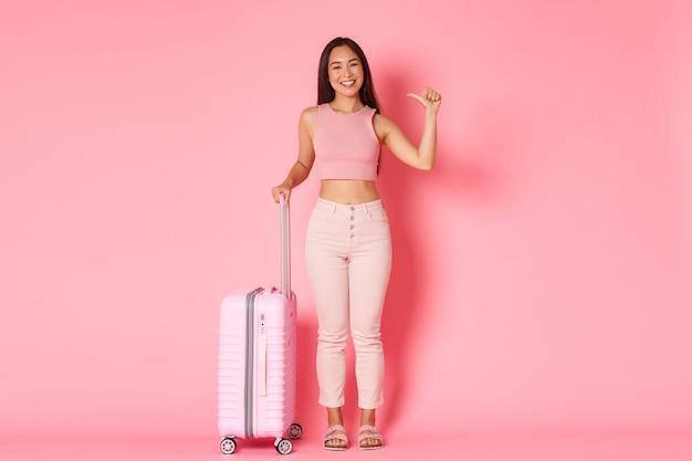 Reizen, vakantie en vakantie concept. volle lengte van brutale en gelukkige aziatische meisjestoerist die zich over roze muur met koffer bevindt en naar zichzelf richt, onderzoekt landen Premium Foto