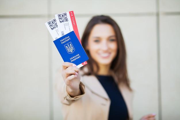 Reizen. vrouw die twee luchtkaartje in paspoort in het buitenland houden dichtbij luchthaven Premium Foto