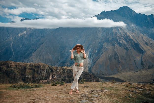 Reizen vrouw toeristische poseren tegen de achtergrond van de bergen en de bewolkte hemel. Premium Foto