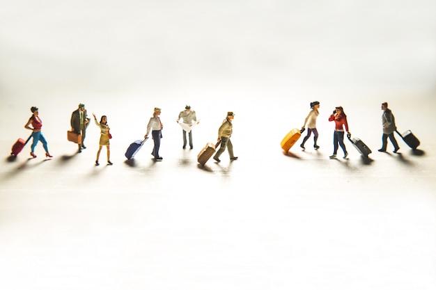 Reizend concept met groep reizigers in miniatuur Gratis Foto