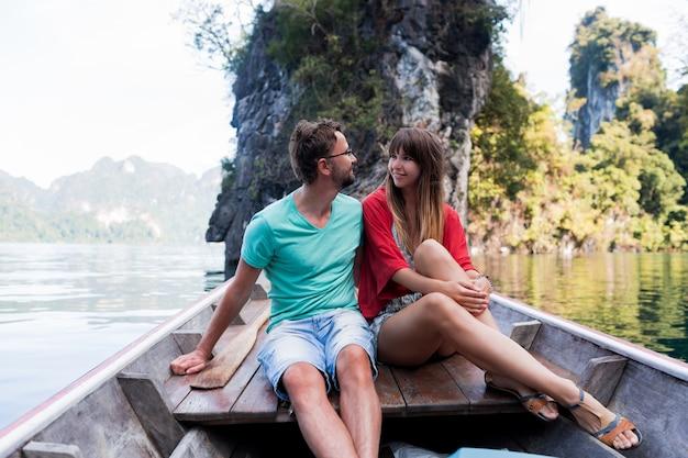 Reizend verliefd koppel knuffelen en ontspannen op longtailboot in de lagune van het thaise eiland. mooie vrouw en haar knappe man vakantie samen doorbrengen. blije stemming. tijd voor avontuur. Gratis Foto