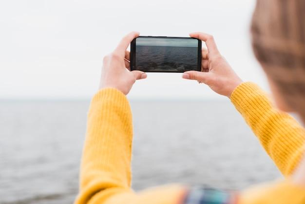 Reizende vrouw die foto van de zee neemt Gratis Foto