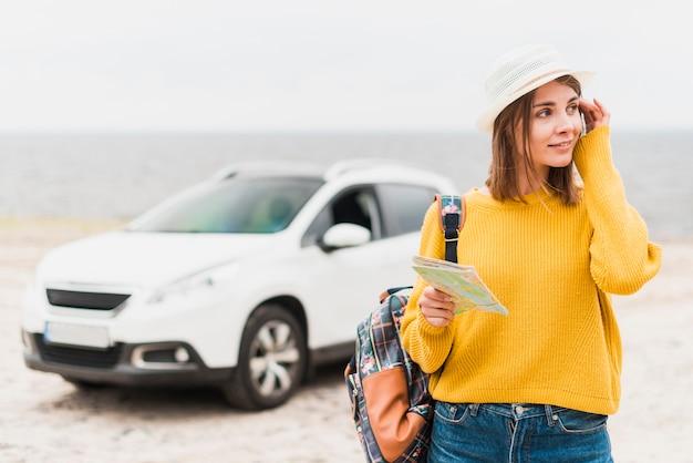 Reizende vrouw met auto op de achtergrond Gratis Foto