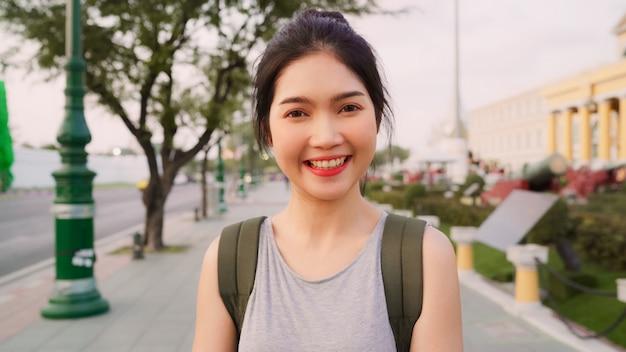 Reiziger aziatische vrouw die het gelukkige glimlachen aan de reis van de cameravakantie voelen in bangkok, thailand Gratis Foto