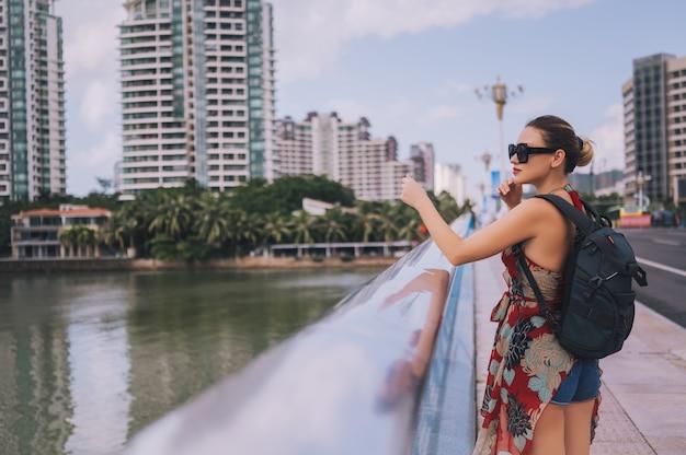 Reiziger blonde backpacker vrouw die in aziatische stad de stad in met wolkenkrabbers lopen. de aard van het reisavontuur in china, toeristen mooie bestemming azië, het concept van de de vakantiereis van de de zomervakantie Premium Foto