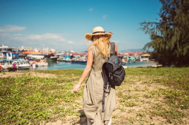 Reiziger blonde backpacker vrouw in strooien hoed achteraanzicht loopt langs de kust bij de pier vissersboten. reisavontuur in de toerist van china. tropische eilandazië. zomervakantie vakantie reis concept Premium Foto
