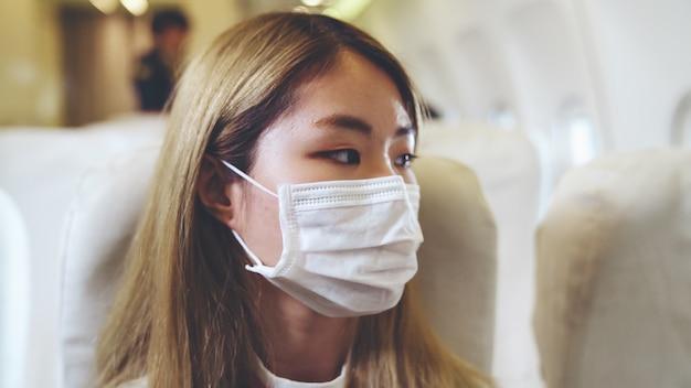 Reiziger die gezichtsmasker draagt tijdens het reizen in een commercieel vliegtuig Premium Foto