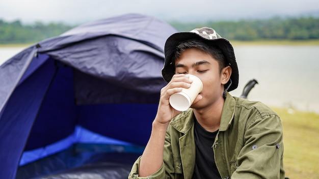 Reiziger man drinkt koffie in het kamp Premium Foto