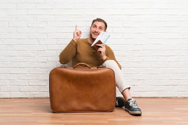 Reiziger man met koffer en instapkaart van plan om de oplossing te realiseren terwijl een vinger omhoog Premium Foto