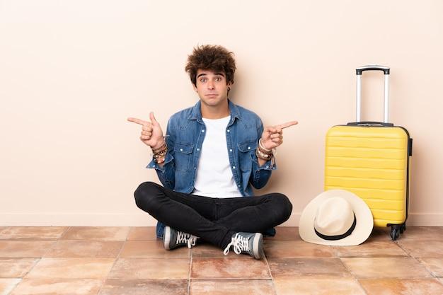 Reiziger man zijn koffer zittend op de vloer wijzend op de zijkanten twijfels Premium Foto