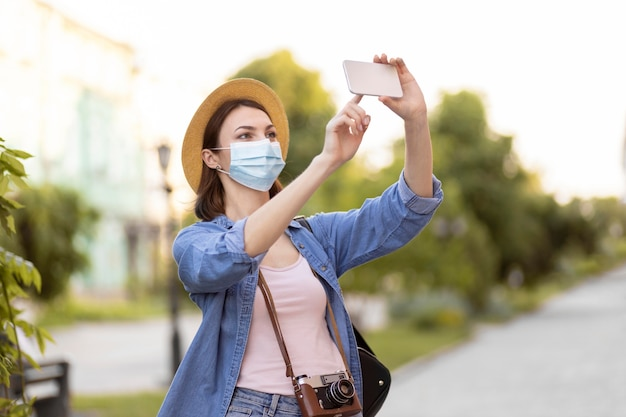 Reiziger met gezichtsmasker en hoed fotograferen Gratis Foto