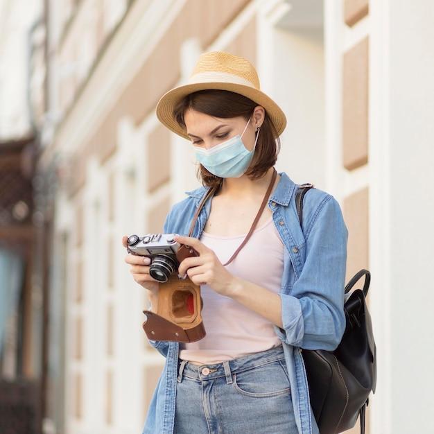 Reiziger met hoed en medisch masker die beelden controleren Gratis Foto
