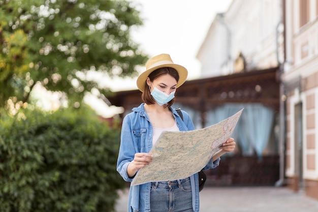 Reiziger met hoed en medisch masker die kaart controleren Gratis Foto