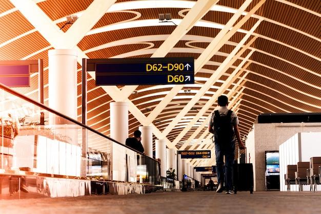 Reiziger met reistas of bagage wandelen in de luchthaventerminal loopbrug voor vliegreizen Premium Foto