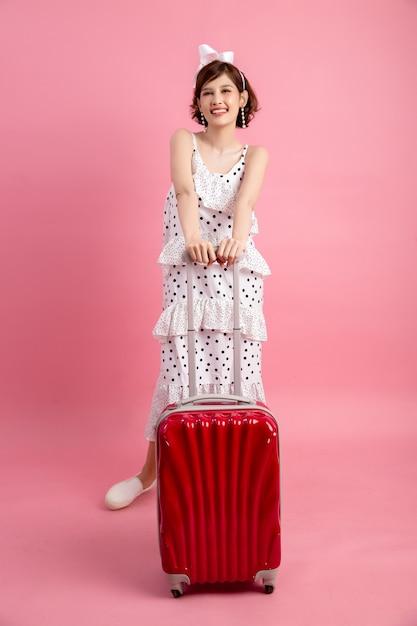 Reiziger toeristische vrouw in zomer vrijetijdskleding met reizen koffer geïsoleerd op roze Gratis Foto