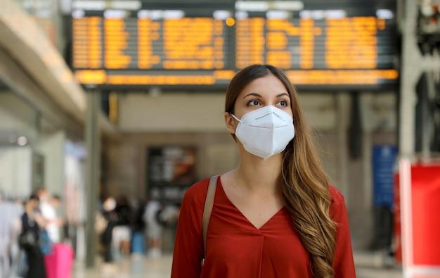 Reiziger vrouw met kn95 ffp2 gezichtsmasker op treinstation ter bescherming tegen virussen en smog. Premium Foto