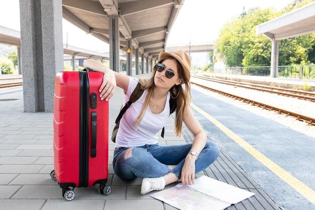 Reiziger wacht op een trein met haar bagage Gratis Foto
