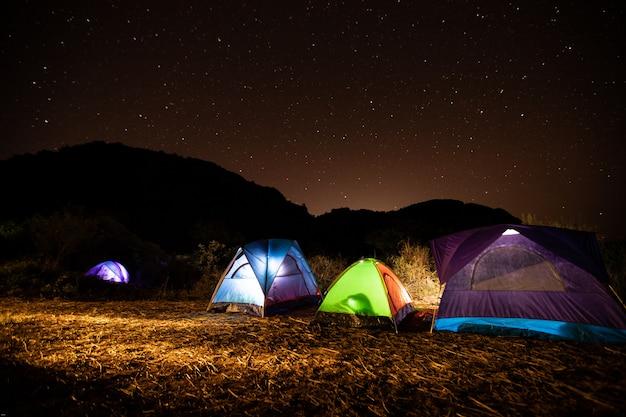 Reizigers tenten 's nachts midden op de berg met de sterren aan de hemel. Premium Foto