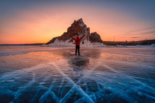 Reizigersmens draagt rode kleren en het opheffen van wapen die zich op natuurlijk brekend ijs in bevroren water bij zonsopgang in meer baikal, siberië, rusland bevinden. Premium Foto