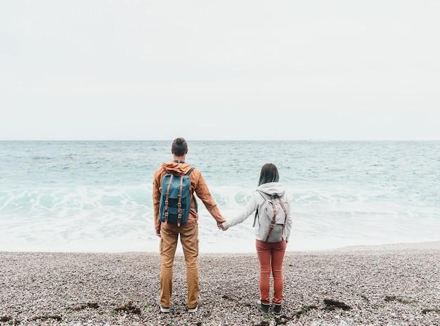 Reizigerspaar dat op zee kijkt. Premium Foto