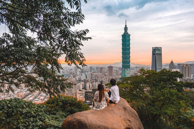 Reizigerspaar en zonsondergang met mening van horizon van cityscape van taipeh taipeh 101 de bouw van de financiële stad van taipeh, de voorraad van taiwan Premium Foto