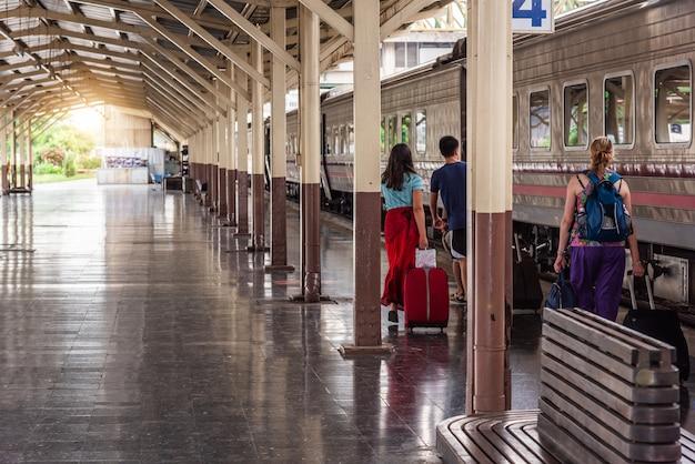 Reizigerstoeristen lopen en slepen bagage om de trein te nemen op het treinstation Premium Foto