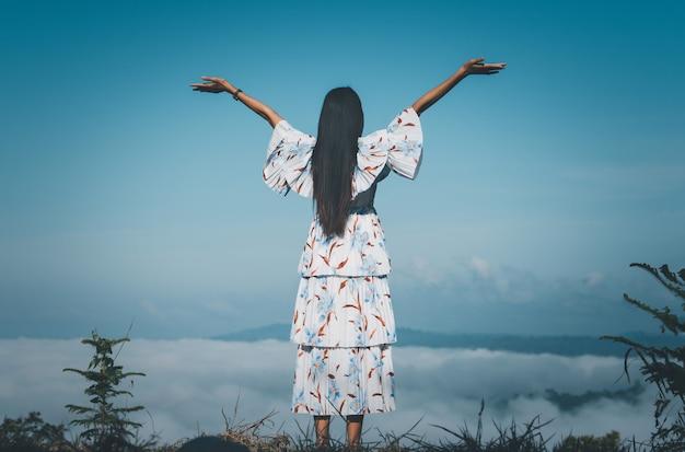 Reizigersvrouw die zich met opgeheven handen bevinden die mistig in de bergen bij zonsopgang kijken. Premium Foto