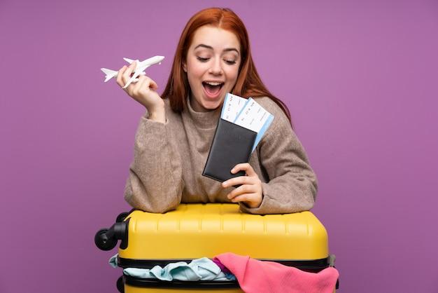 Reizigersvrouw met een koffer vol kleren en met een paspoort Premium Foto