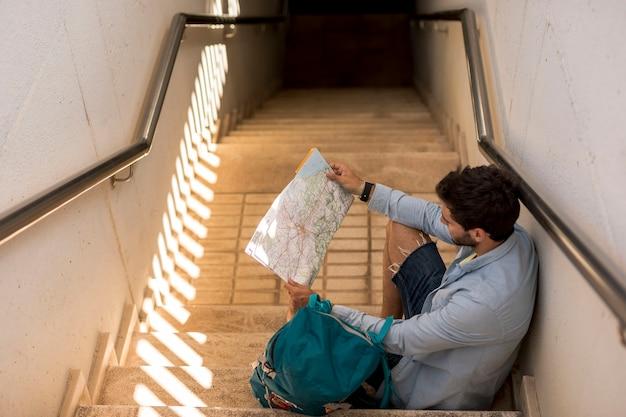 Reizigerszitting op treden en het kijken op kaart Gratis Foto
