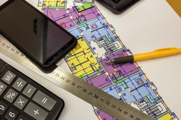 Rekenmachine, pen en liniaal bij het bouwen van huisarchitectuur plan tekening blauwdruk. planning, meting en investeringen. Premium Foto