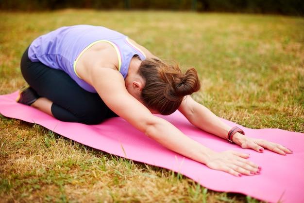 Rekken is erg belangrijk na fysieke oefeningen. jonge vrouw doet yoga buiten. Gratis Foto