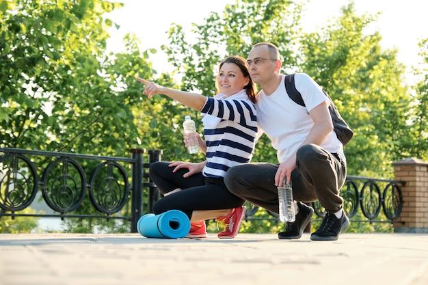 Relatie tussen mensen van middelbare leeftijd, paar praten, ontspannen na fitness in park Premium Foto
