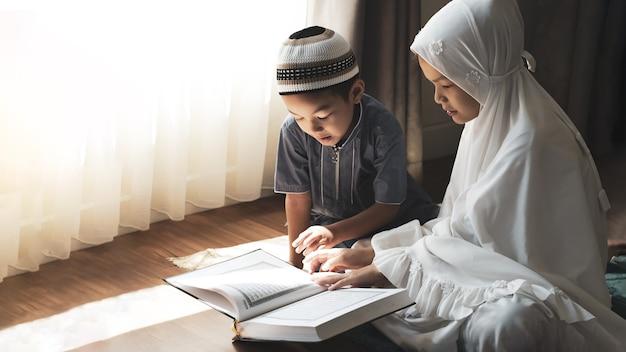 Religieuze aziatische moslimkinderen leren de koran en bestuderen de islam nadat ze thuis tot god hebben gebeden. het licht van de zonsondergang schijnt door het raam. vreedzaam en wonderbaarlijk warm klimaat. Premium Foto