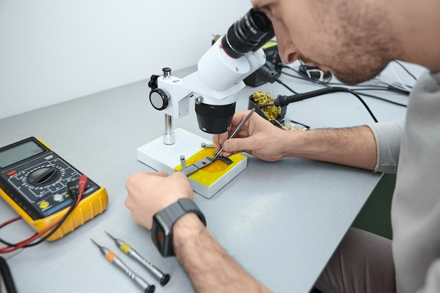Reparateur onderzoekt het moederbord van de mobiele telefoon onder de microscoop in laboratorium Gratis Foto