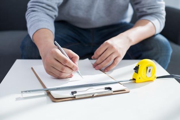 Reparatie, gebouw en huis concept - close-up van mannelijke handen schrijven in klembord Gratis Foto