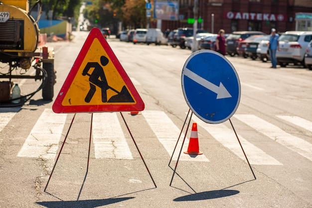 Reparatie van wegen. waarschuwingsborden over reparatiewerkzaamheden aan bestrating. aandacht omweg Premium Foto