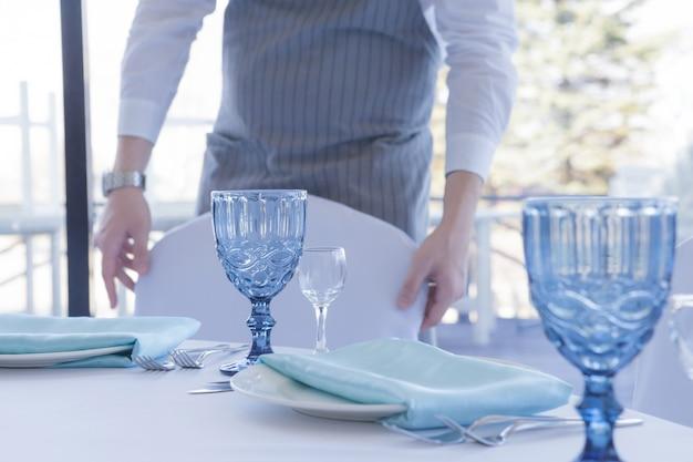 Restaurant de ober serveert een tafel voor een huwelijksfeest, beweegt een stoel Premium Foto