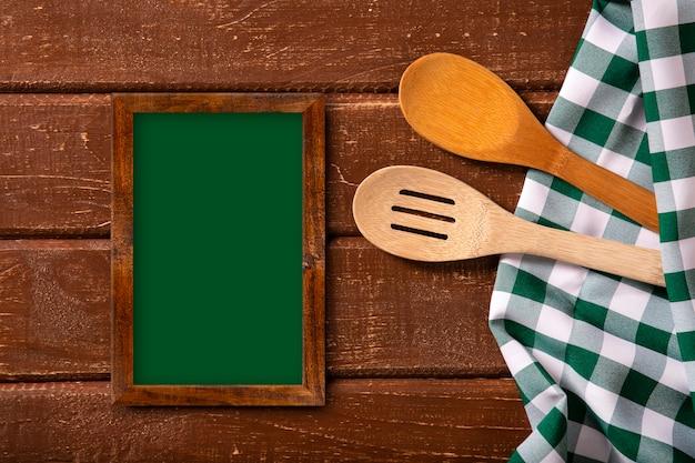 Restaurant menu. bovenaanzicht van schoolbord menu tot op het rustieke houten bureau met lepels en groene servet Premium Foto