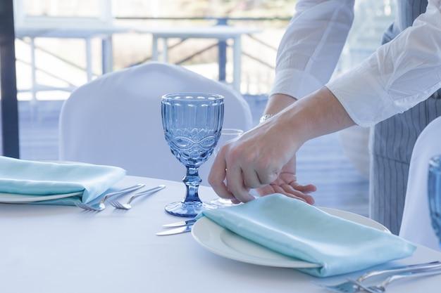 Restaurant ober serveert een tafel voor een huwelijksfeest, close-up Premium Foto