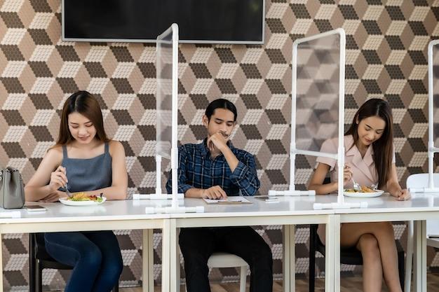 Restaurantklanten hebben een stoel met tafelafscherming voor sociale afstand Premium Foto
