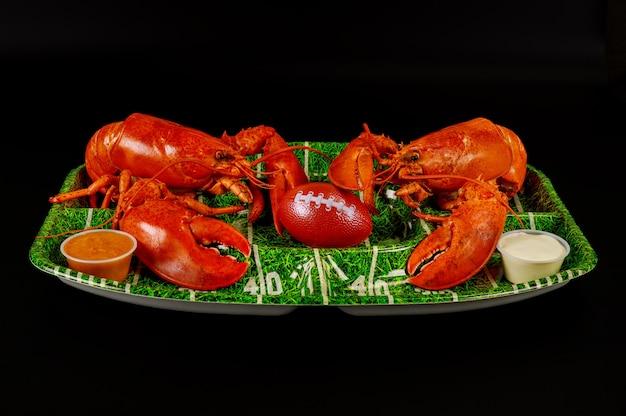 Restaurantvoedsel voor feesten in american football. rode zeekreeften op groene plaat met bal. Premium Foto