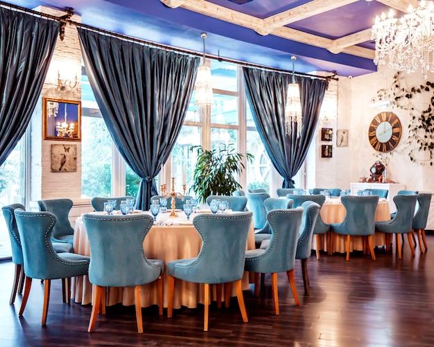 Restaurantzaal met blauwe stoelen en decors op de muur Gratis Foto