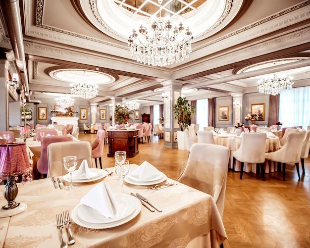 Restaurantzaal met ronde en vierkante tafels, stoelen en planten Gratis Foto